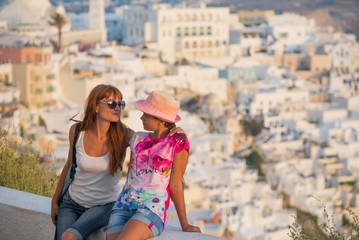 concept of family tourism and travel. Mom and daughter on a background of sunset city. Two girls tourists travel to the island of Santorini, Greece. Sunset on the most beautiful island