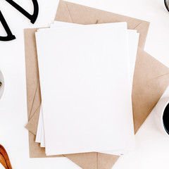 Workspace with clean paper blank, coffee, craft envelope, scissors, office supplies on white background. Flat lay, top view office table desk.