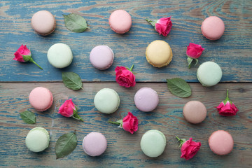 Macarons flat lay withroses and leaves on green wooden background. Top view