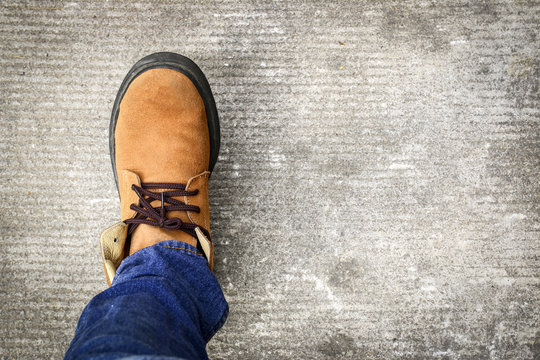 A man wears jeans and leather shoes on concrete floor background.