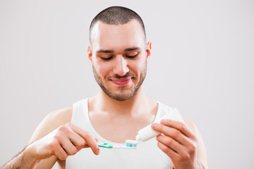 Young man holding toothbrush. Dental hygiene concept.