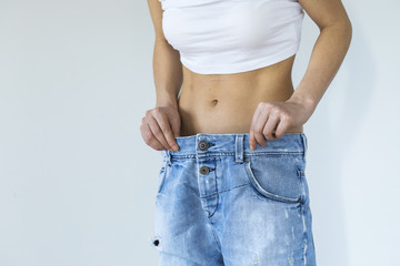 Weight loss woman with old jean on gray background