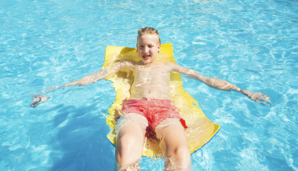 Teenager in red swimming trunks relaxes in the pool