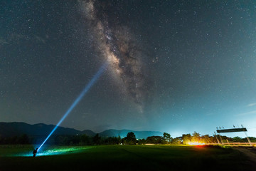 Man with a flashlight, Milky way galaxy with stars and space dust in the Green Terraced Rice Field in Thailand