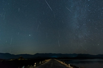 Shooting star and milky way over reservoir with mountain night sky.