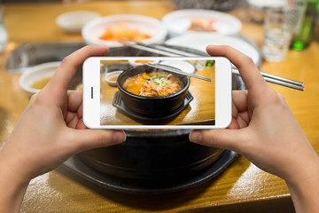 A woman photographs a bowl of soup on the smartphone in the restaurant.