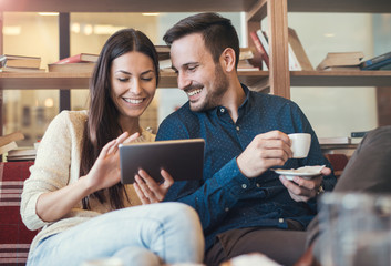 Young couple drinking coffee in cafeteria and having fun with tablet, surrounded with books on the wooden shelves