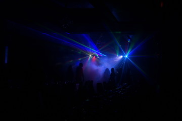 Deejay silhouette on a stage with big disco ball at background with the colorful rays on it