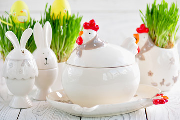 Easter dishes in the form of chickens and rabbits on a white wooden background.