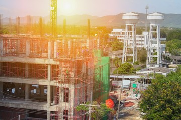 Construction and renovation of tall building  under in scaffolding in Thailand  with sunset light tone.