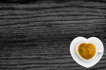 White coffee cup in shape of heart on black wood texture background