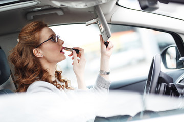 Beautiful businesswoman fixing her makeup while waiting in the car.Using lipstick.