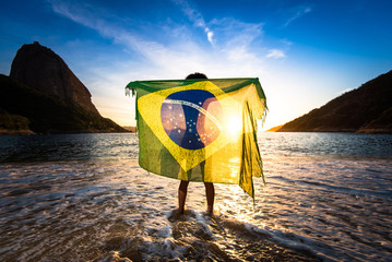 Girl Standing in Water and Holding Beach Yoke With Brazilian Flag by Sunrise, in Rio de Janeiro, With the Sugarloaf Mountain in the Horizon