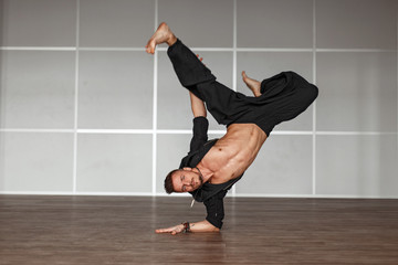 Handsome man dancer dancing. Man stands on hands in a dance pose.