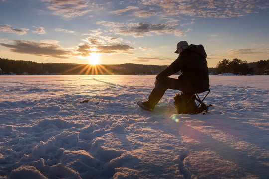 Ice fishing on a lake in Norway at sunset.