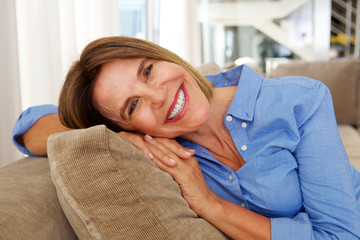 elderly woman smiling on sofa at home
