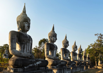 silhouette big ancient buddha statues sitting in row on public thai temple on blue sky background