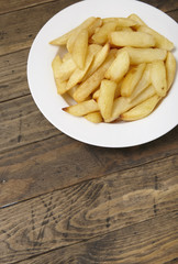 A bowl of French fries on a rustic wooden table background with blank space below