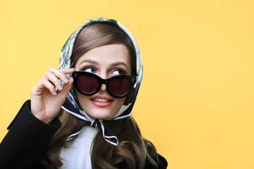 Fashion retro style portrait of young beautiful woman in sunglasses on yellow background