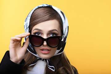 Fashion retro style portrait of beautiful surprised woman in sunglasses on yellow background