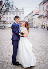Bride and groom admire each other standing on old city square