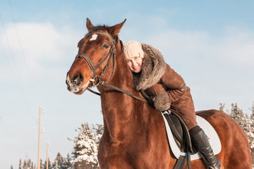 Woman in brown dress and brown horse in a winter
