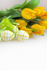 Bouquet of fresh yellow tulips with easter eggs