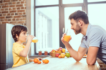 Foto op Canvas Sap Side view of happy father and son drinking fresh juice together