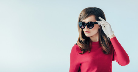 Fashion retro style portrait of young beautiful woman in sunglasses on white background