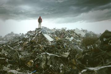 Mann steht auf riesigem Schutthaufen
