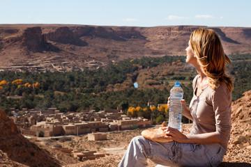 femme assise sur une montagne devant un village marocain
