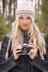 Young attractive woman with an old camera
