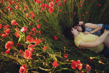 a young man and his woman  lying in a field of poppies