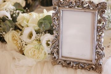 Quadretto, argentato con fiori bianchi su tavolo addobbato