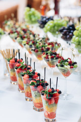 The vases with fruits stand on the buffet table