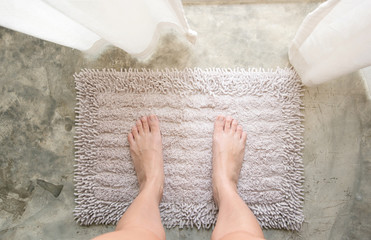 Woman feet standing on old white or grey carpet with her bare feet in bathroom.