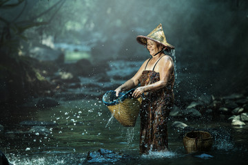 Old Asian woman bathing creek to cool.