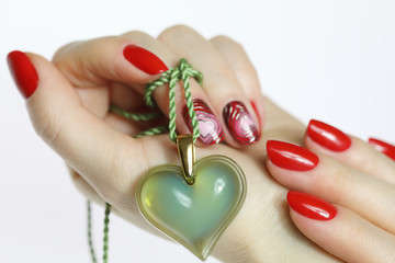 Manicure with painted hearts. Manicure nail paint . beautiful female hand with colorful nail art design manicure.