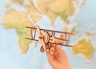 woman's hand holding toy airplane against map of world. empty space for your text or information.