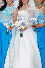 The bride with bridesmaids keep bouquets and stand in the street