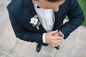young groom in blue jacket looks at his wrist watch