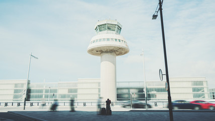 Rear view of tired man with luggage waiting for taxi after his arrival in Barcelona, silhouette of young guy with several suitcases in front of air traffic control tower of modern contemporary airport