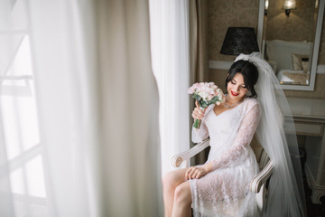 beautiful and young bride in veil with bouquet of flowers sitting on the chair