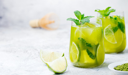Matcha iced green tea with lime and fresh mint on a marble background. Copy space
