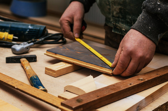 Carpenter using tape measure.