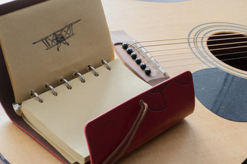 Leather notebook with black pen picture of an airplane on the background of a guitar