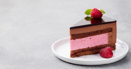 Chocolate and raspberry cake, mousse dessert on a white plate. Copy space