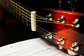 Guitar headstock and tuning pegs closeup against a blues sheet music in the darkness