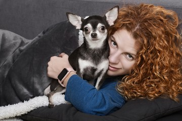 beautiful woman with curly red hair and her chihuahua dog