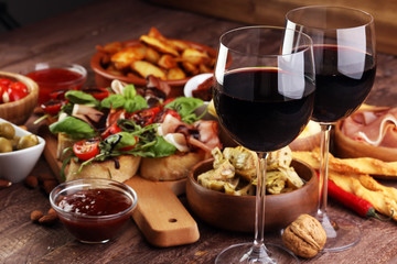 Fototapeta Italian antipasti wine snacks set. Cheese variety, Mediterranean olives, pickles, Prosciutto di Parma, tomatoes, artichokes and wine in glasses